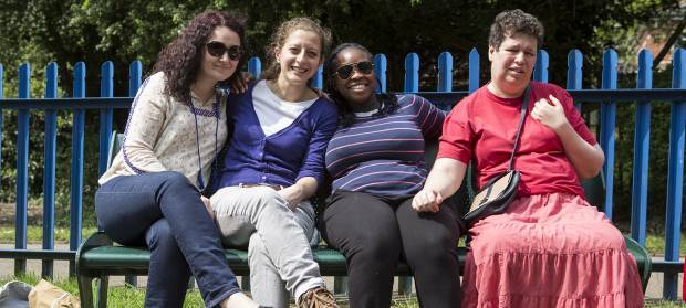 Four women sat together outside in the sunshine on a park on a bench, blue metal fence railing in the background