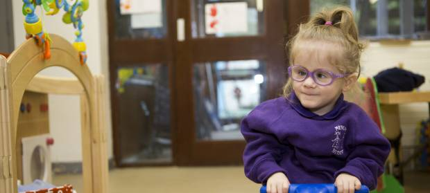 Small child wearing glasses and purple jumper sat in nursery
