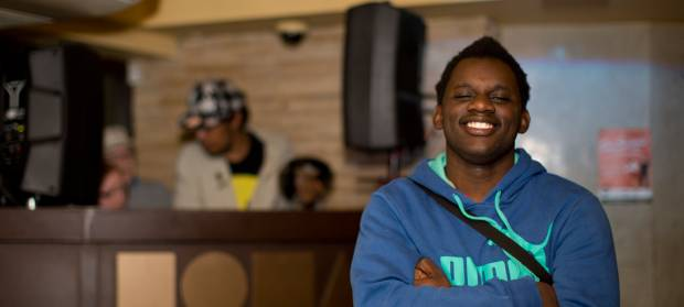 Young man wearing blue jumper smiling into camera.