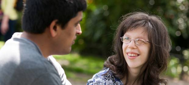 Woman with long dark hair and glasses sat outside in park looking at man who is sat next to her.