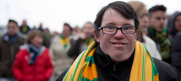 Man with glasses stood in crowd outside at football match, wearing a yellow and green football scarf, smiling at the camera