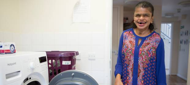 Smiling woman stood in laundry room next to washing machine holding clothes in her hand.