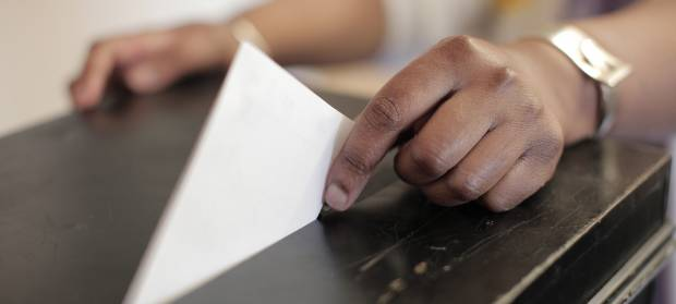 Hand placing voting slip in a ballot box.
