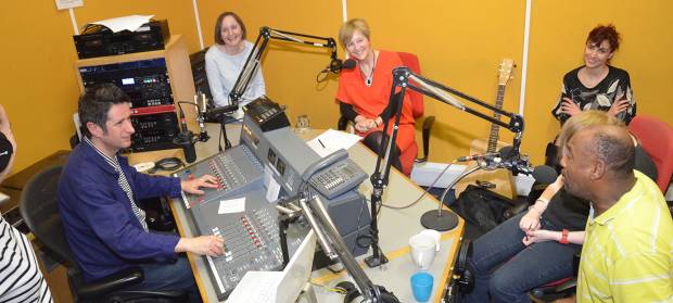 Group of people sat round table in a radio studio
