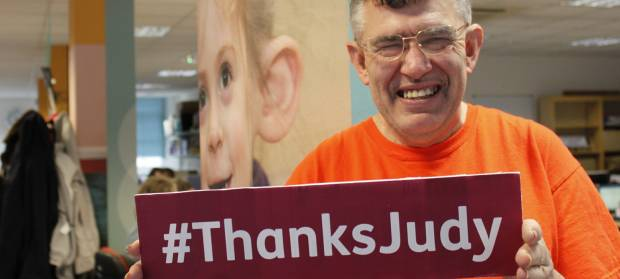 "Man smiling at camera holding a sign that reads ""#ThanksJudy"""