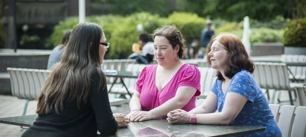 Three women sat together around a picnic table outside.