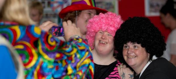 People wearing large wigs and fancy dress stood together smiling at party.
