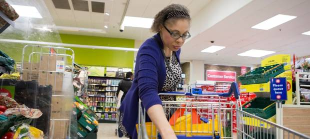 Woman in supermarket placing items into her trolley.