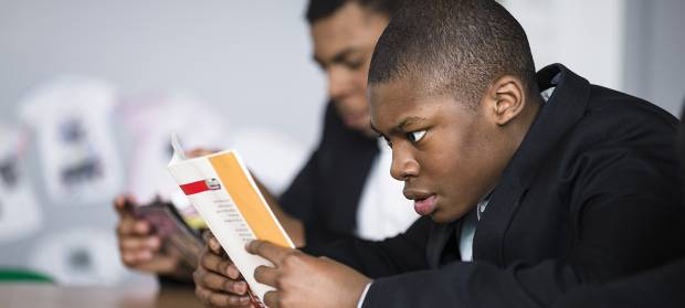 Schoolboy sat at desk in classroom reading a book.