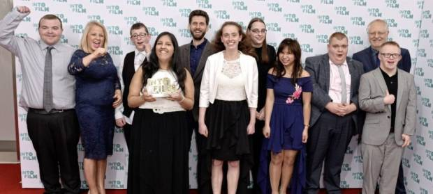 Group of people stood on red carpet at awards ceremony.