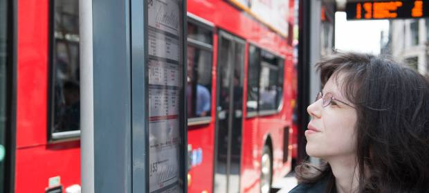 Woman with long dark hair and glasses stood at bus stop where red bus is stopped, looking at timetable.