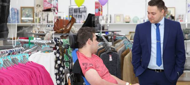 Man in suit stood talking to man using wheelchair next to him, in shop.