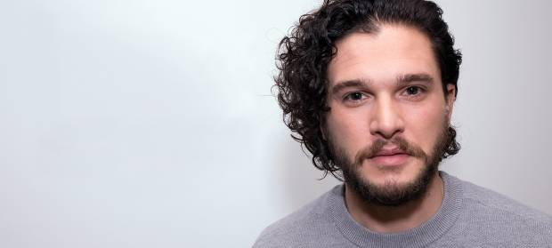 Man, Kit Harington, with dark curly hair stood against white background looking into camera