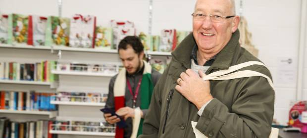 Man looking into camera whilst stood in Mencap charity shop and holding bag on his shoulder.