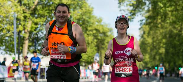 Woman wearing Mencap vest runs outside with male guide runner next to her