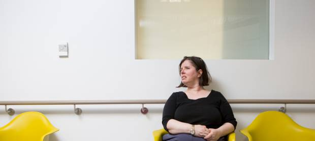 Woman looking off to the side whilst sat on yellow chairs in white corridor