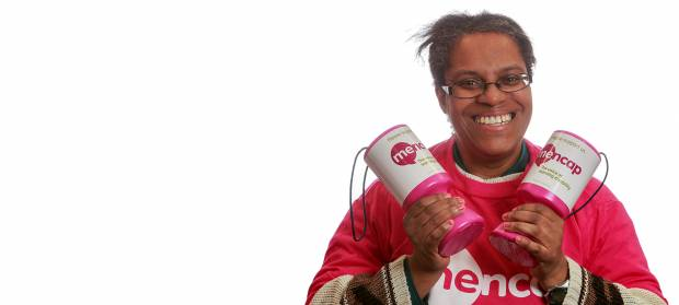 Woman smiling looking into camera. She is wearing a pink Mencap t-shirt and holding Mencap collection pots in her hands.