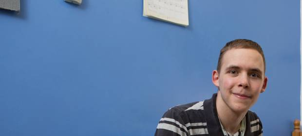 Young man sat in bedroom against blue wall. He is smiling into camera.