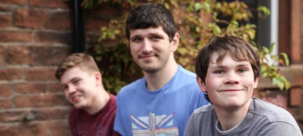 Three young man smiling into camera whilst sat outside house.