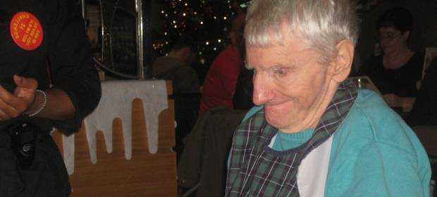 Old man with white hair smiling sat in restaurant