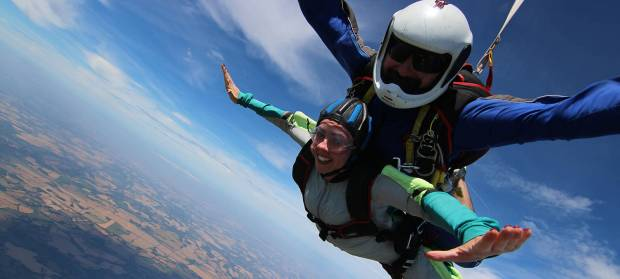 Two people strapped together doing a skydive.