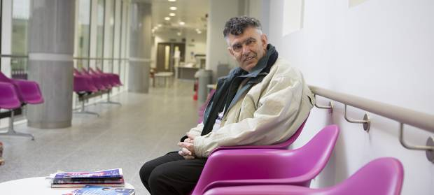 Older man sat in hospital corridor