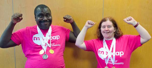 A man and woman stood next to each other with their arms raised. Both are wearing Mencap t-shirts and have medals round their necks