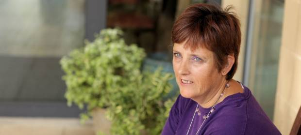 Woman with short hair wearing a purple top is sat outside next to plant