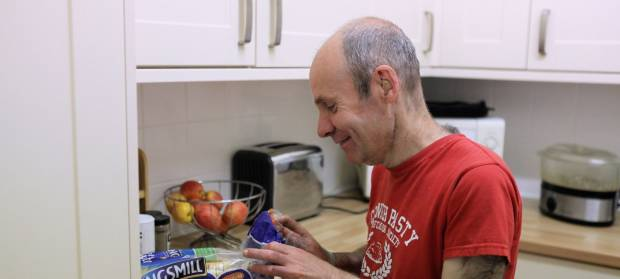 Man wearing red t-shirt stood in kitchen, he is smiling as he opens a packet of bread.
