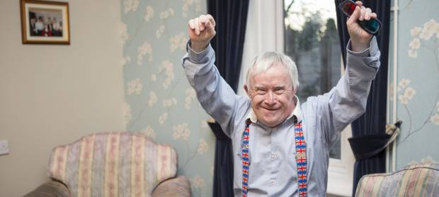 Smiling older man with shirt and Union Jack braces stood in living room raising his arms in the air in celebration.