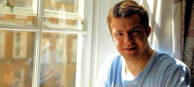 Young man wearing blue top smiling into camera whilst sat next to window.