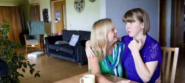 Mother and daughter with arms around each other, sat talking together at dining room table