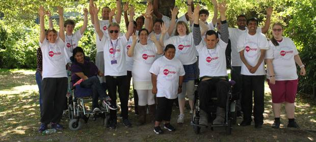 Group of people wearing Mencap t-shirts stood outside cheering.