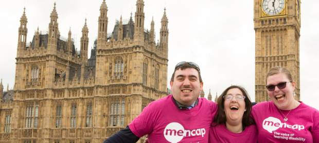 Two women and a man wearing Mencap t-shirts stood together smiling and laughing in front of the Houses of Parliament in London.