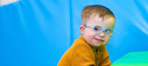Young boy wearing a yellow jumper and glasses looking into camera playing in a soft play area
