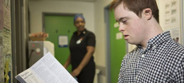 Young man stood in hospital corridor reading leaflet
