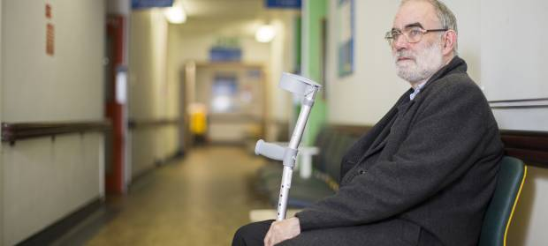 Older gentleman holding crutches sat on a chair in a hospital waiting room