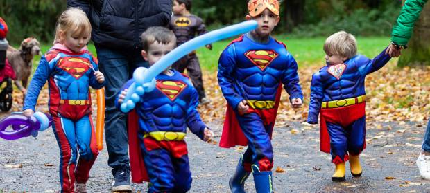 Four young children dressed in Superman outfits, walking through park.