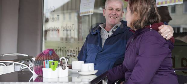Man and woman sat together at a table outside a cafe. The man has his arm round the woman's shoulders.