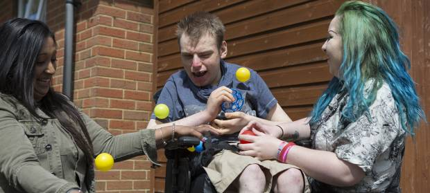 Three people sat outside in garden playing with yellow plastic balls.